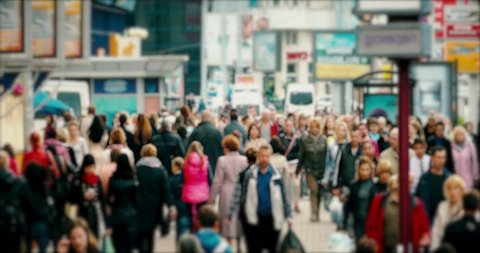 Crowd on a busy street. Anonymous crowd of people walk down a busy street with advertising, billboards, cars and public transport.