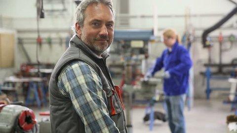 Portrait of plumber standing in workshop