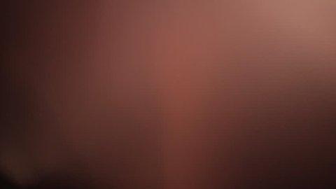 Subtle light leak on black background, moving lens flare. Red - orange - blue pastel colors. Overlay on top of footage for vintage super 8 film effect.