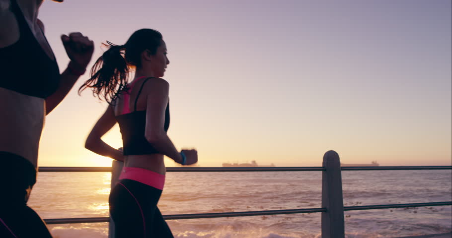 Two athletic woman running outdoors in slow motion on promenade at sunset near ocean enjoying evening run RED DRAGON #10634096