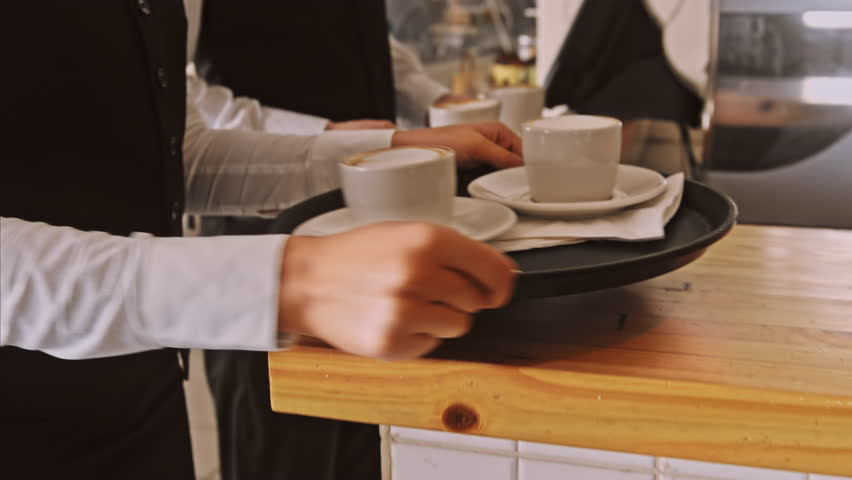 4k medium steadicam video of waiter and coffee on a tray, walking to a customer in hotel or restaurant cafe.