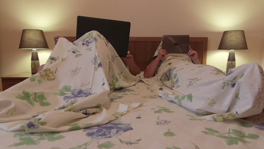 Adult Married Couple In Bed Lying Side By Side Using Gadgets   HD Stock  Video Clip