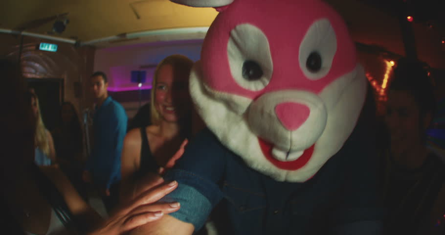 Group of friends at a party with one wearing a plush rabbit head | Shutterstock HD Video #10655663