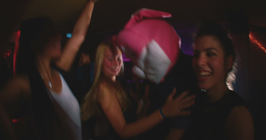 Group of friends at a party with one wearing a plush rabbit head #10655666