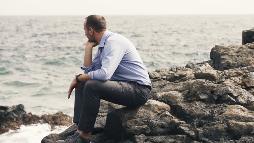 Rocks In Spanish Part - 35: Young Businessman Relaxing While Sitting On Rocks Near Sea - HD Stock  Footage Clip