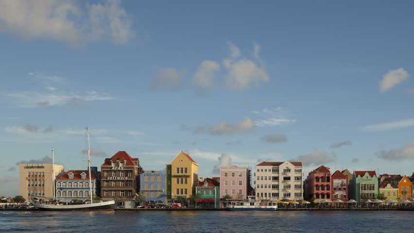 WILLEMSTAD, CURACAO - DEC 19, 2013: 4K Time lapse pan shot of the waterfront with historic colorful caribbean architecture and seafront esplanade with ships passing the open Queen Emma Pontoon Bridge.