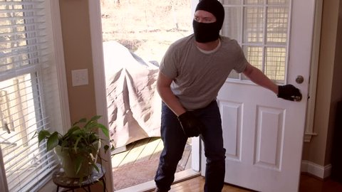 A man who is a thief and burglar breaking into a house through the back door while wearing a ski mask and walking towards the camera to look directly into the lens close up and wide eye.