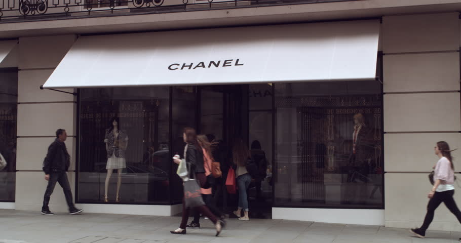LONDON - CIRCA 2015: Shot of luxury goods boutique Chanel store front in Central London as shoppers pass by in the foreground.