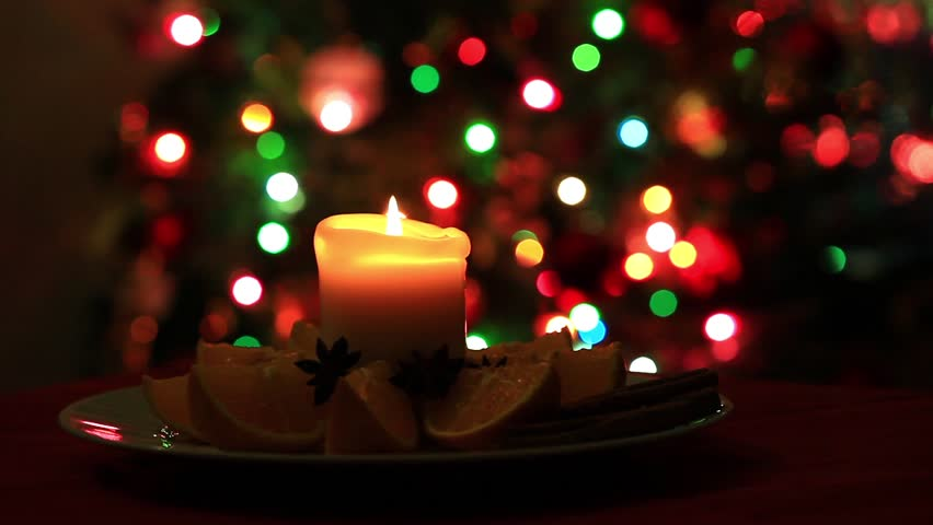 flame of candle on blurred blinking christmas lights background hd stock video clip - Christmas Lights Video