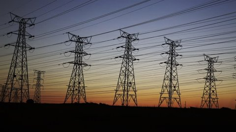 Pan of electrical power lines and pylons at dusk