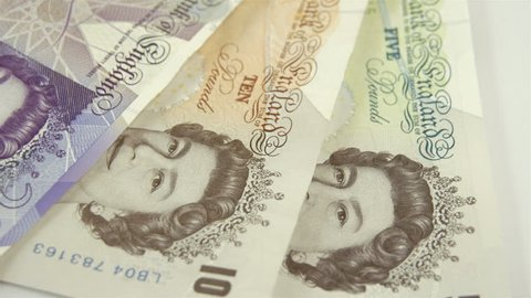 Rotating view of the England Pounds bill on the table. Showing the 5 10 and 20 Pounds bills with different colors