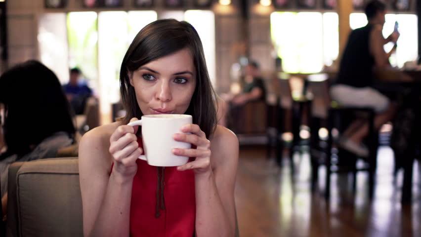 Sad, pensive woman drinking coffee sitting in cafe   | Shutterstock HD Video #10759679