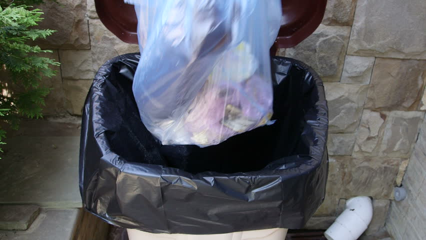 Hand putting plastic garbage bag into waste bin container