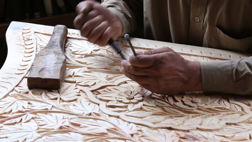 Indian man are making wooden souvenirs for tourists in Srinagar, India. Wood Carving is a traditional handicraft in Kashmir.