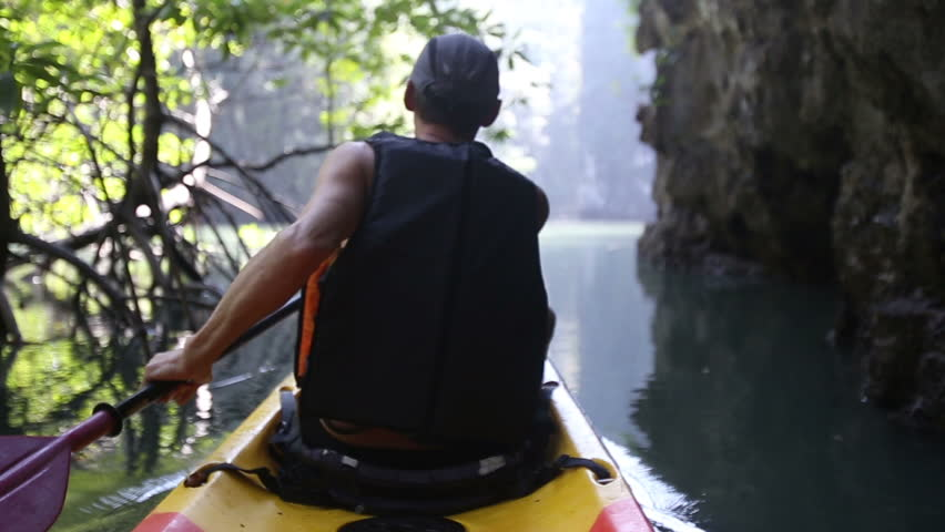 european man backside view in safity vest rows on kayak out of jungle to freshwater in canyon