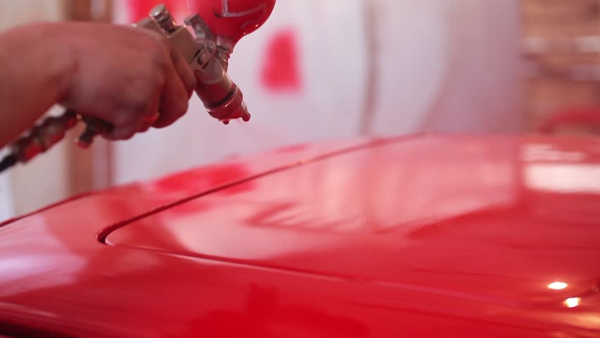 Painter paints the red car in garage.