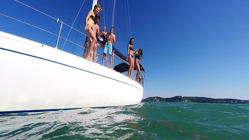 Happy people jumping into water from a boat - Friends diving and having fun on a summer vacation - Tourists on excursion with a sailing ship | Shutterstock HD Video #10798322