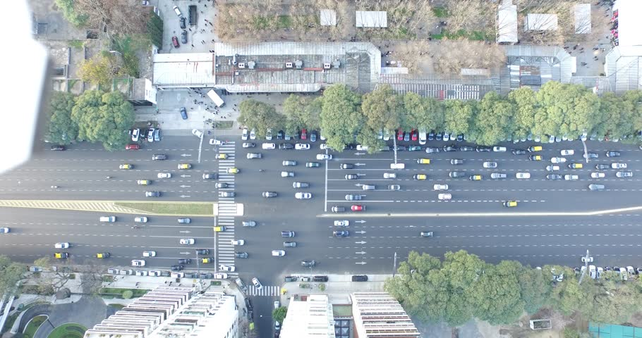 Aerial, top drone scene of city traffic. Cars, trucks, public transport and pedestrians movement are filmed. Traffic lights stops the city movement. Buenos Aires, Argentina.
