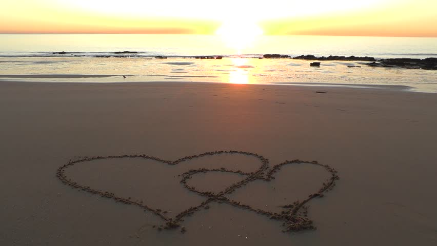 Close Up Of Love Heart Symbols In The Sand Remote Tropical Beach At Sunset With Waves Ocean And Sun Background Copy Space