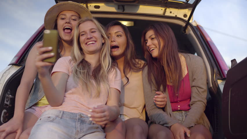 Group Of Wild And Fun Teens Hang Out In Back Of SUV, Girl Grabs Friend's Phone To Take Selfies (4K) | Shutterstock HD Video #10811918