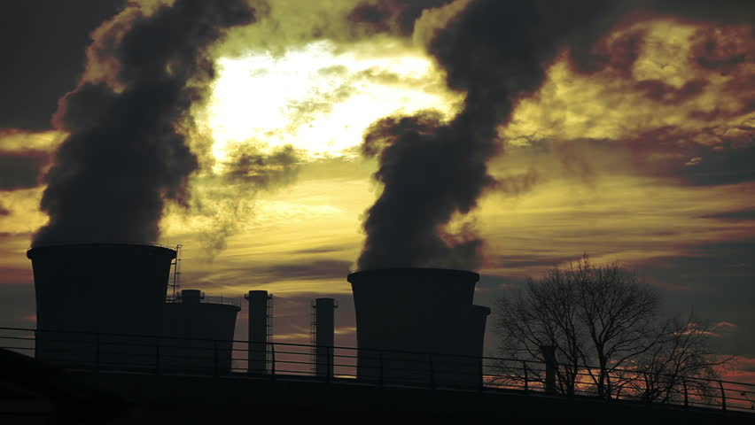 Power plant. Visible flock of birds. Smoke, steam, pollution discharged from a coal powered electrical generation facility.
