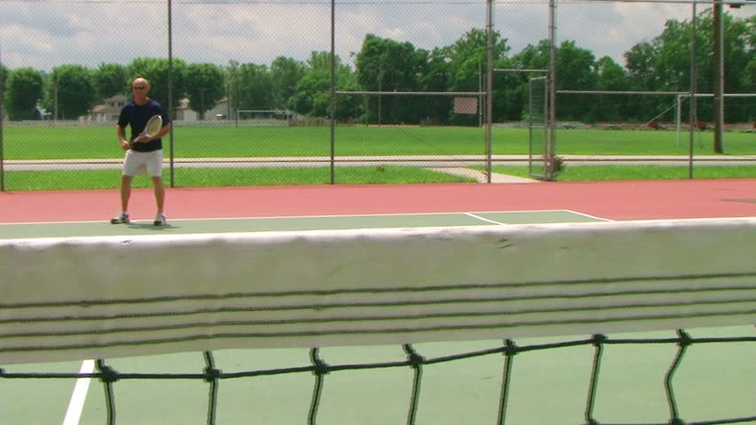 Tennis player volleys using forehand technique, crane shot across net.