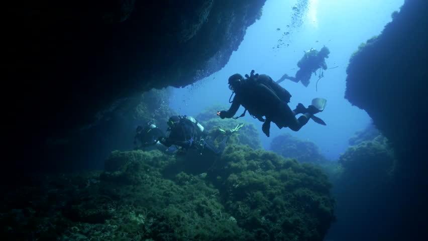 Underwater shot of scuba divers entering a huge underwater cave in mediterranean sea, wide shot, ustica island, italy | Shutterstock HD Video #10833632