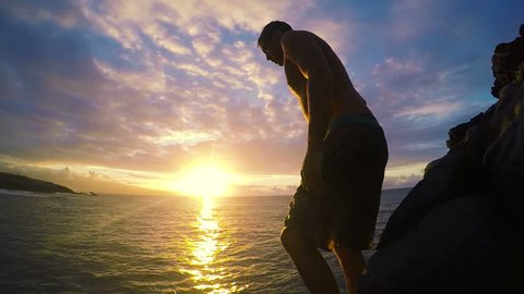 Young Man Does Front Flip off Clip into Ocean at Sunset at Medium Speed.