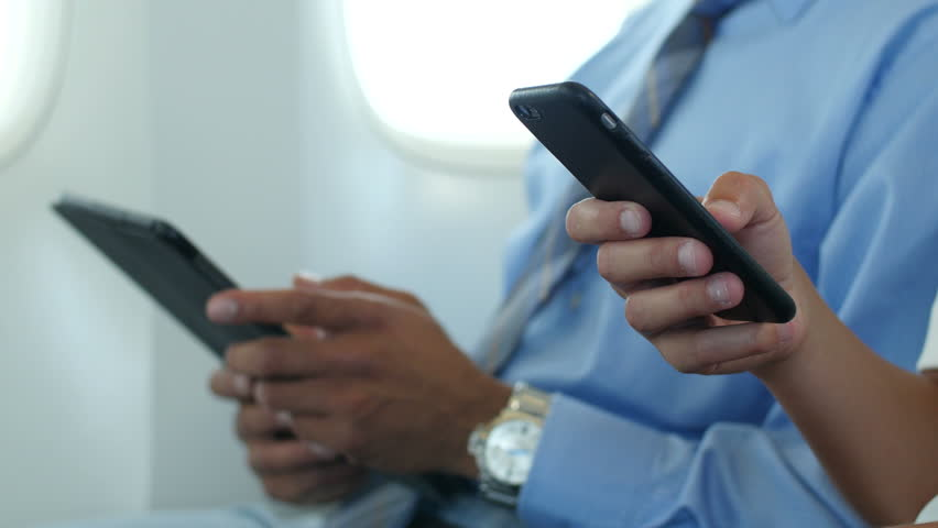 Hands holding electronic devices/phone on a plane, extreme close up of the phones | Shutterstock HD Video #10853066