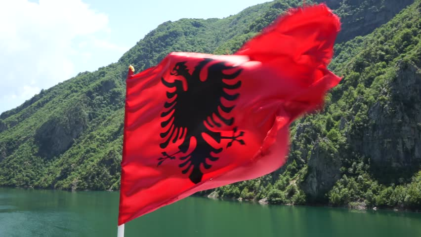 KOMAN, ALBANIA - 12 JUNE 2015: The flag of Albania on a windy hot summer day. Boat trip from Koman to Fierza on Alpin Ferry