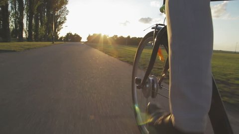 close-up of the front wheel of a bicycle and a man who cycling towards sunset