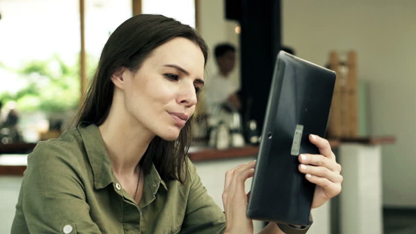 Young happy woman with tablet computer sitting in cafe  | Shutterstock HD Video #10880306