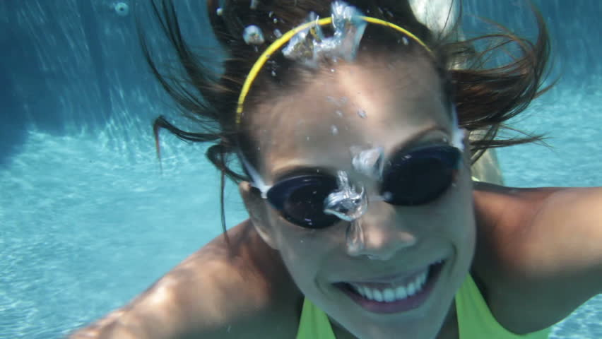 Woman swimming underwater in pool smiling happy giving thumbs up sign hand waving hands saying hello looking at camera. Young female swimmer with swim goggles at holiday resort.