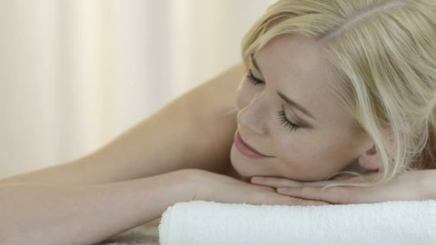 Closeup of beautiful young woman relaxing on massage table with eyes closed. Relaxed caucasian girl with blonde hair relaxing at spa center. Close up face of beautiful woman lying on table massage.