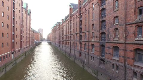 Old red-brick buildings in Speicherstadt along a canal with bridges in Hamburg, Germany