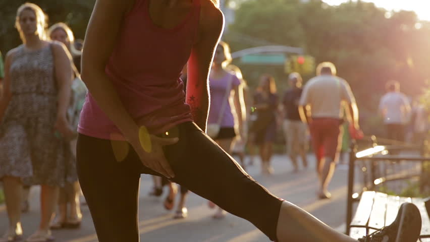 NEW YORK - JULY 25, 2015: athletic woman in pink tank top stretches in Central Park at sunset in summer, NY. Central Park is a public park in Midtown Manhattan where many athletes go to train.