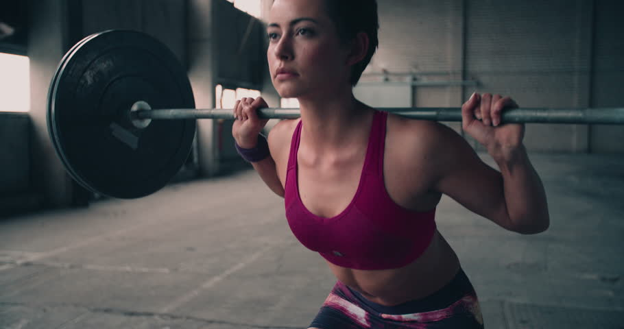 Full length image of a young woman testing her strength by holding a barbell with heavy weights on her shoulders as she squats