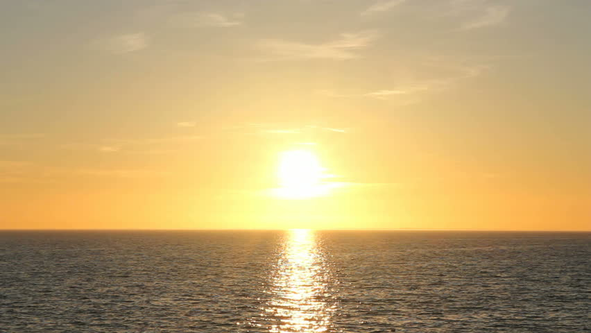 The bright sun is setting over water with gentle waves