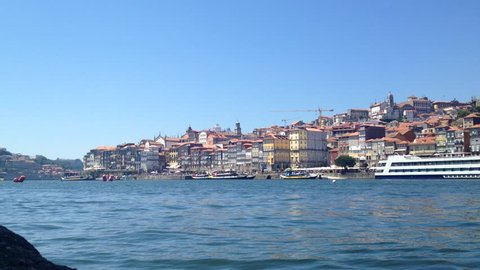 PORTO, PORTUGAL - AUGUST 1, 2015: The typical colorful buildings of the Ribeira District and the Douro River with the river cruise boats in the city of Porto, Portugal. Unesco World Heritage.