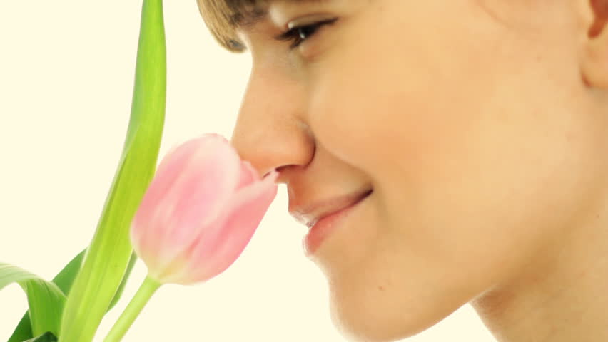 Young attractive woman smelling spring tulip, isolated