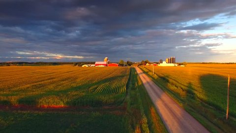 The American Heartland At Sunset. A country road, corn fields, farms and a dramatic sky conspire to make a uniquely beautiful landscape.