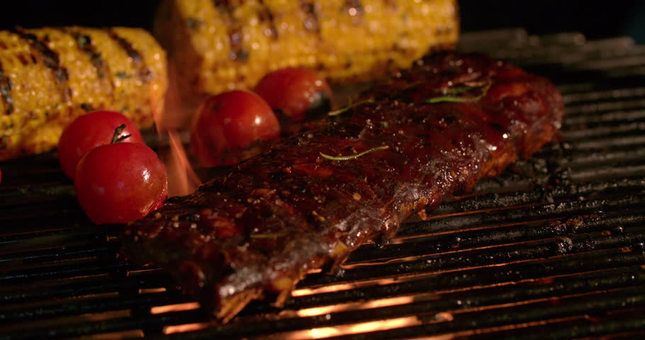 Night time barbecue with tender ribs, small tomatoes and corn grilling over the glowing coals in Slow Motion
