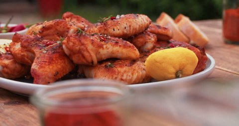 plate of spicy chicken wings sprinkled with chillie and herbs on a vintage wooden table with condiments