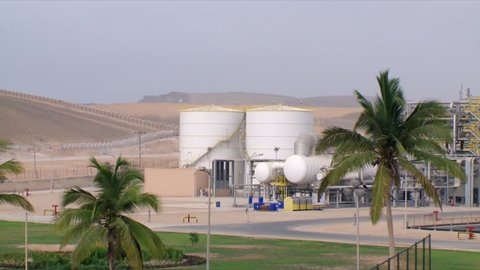 A zoom in shot to large white cylindrical industrial buildings in Salalah in Oman, showing date trees and the desert background.