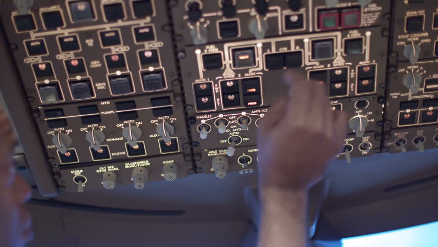 Detail shot of airline pilot switching various controls on an overhead panel in a jumbo jet cockpit.  Originally recorded in 4K.