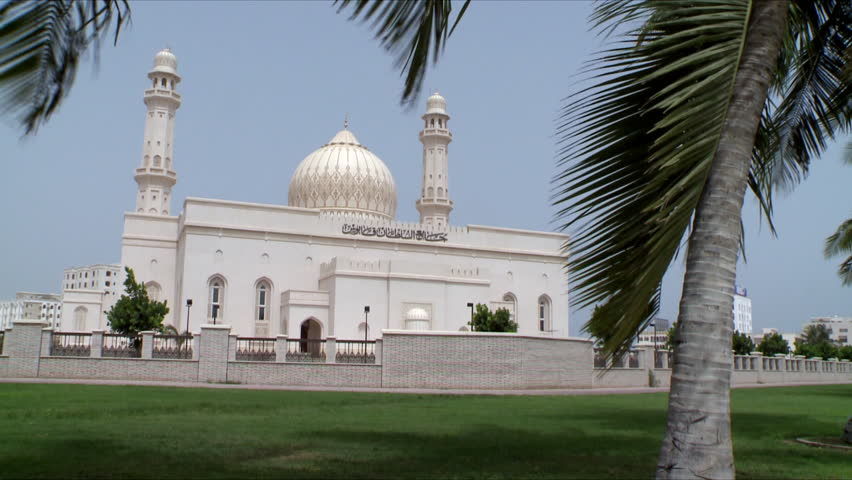 A static shot of a white mosque in Salalah, Oman with branches of date trees blowing in the wind