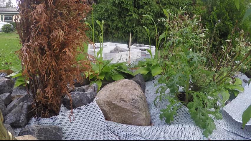 Gardener Landscaping With Stones, In The Garden   4K Stock Footage Clip