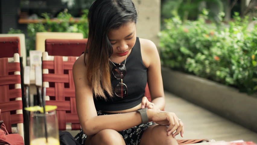 Young woman reading a tablet or ebook in a train station while is pretty woman with smartwatch sitting in cafe hd stock footage clip fandeluxe Ebook collections