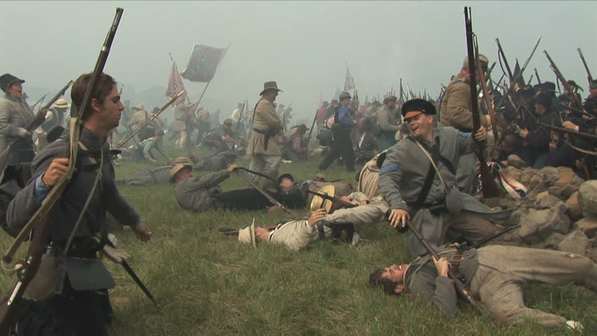 PENNSYLVANIA - JULY 2008 - large-scale, epic Civil War anniversary reenactment -- in the middle of battle.  Battle of Gettysburg, Confederates attack in Pickett's Charge, combat deaths, flag charge.