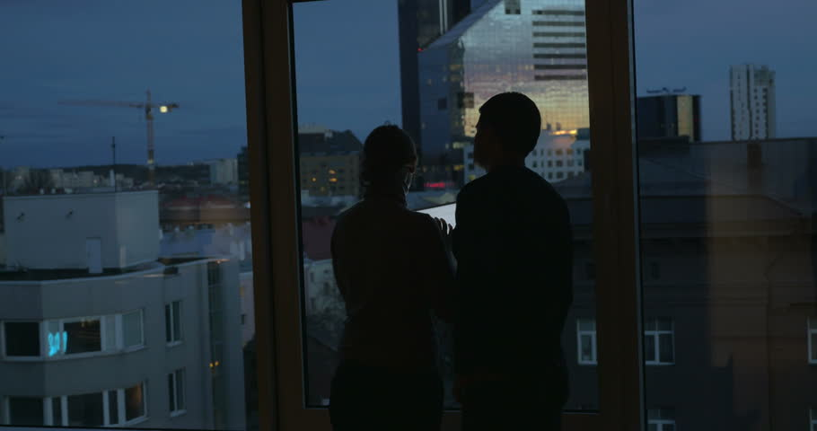 Man and woman using tablet computer standing by the window at home at night. City panorama can be seen through the glass